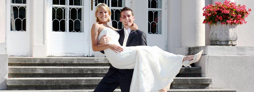 Der Bräutigam trägt seine Braut die Stufen herauf.