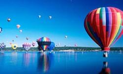 Heissluftballons spiegeln sich in einem See