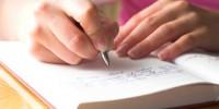 In das Hochzeitsgästebuch wird etwas eingetragen.