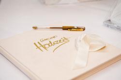 Ein Hochzeitsgästebuch mit Stift liegt für die Gäste bereit.