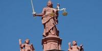 Justizia mit verbundenen Augen, Schwert und Waage.