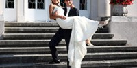 Der Bräutigam trägt seine Braut die Stufen herunter..