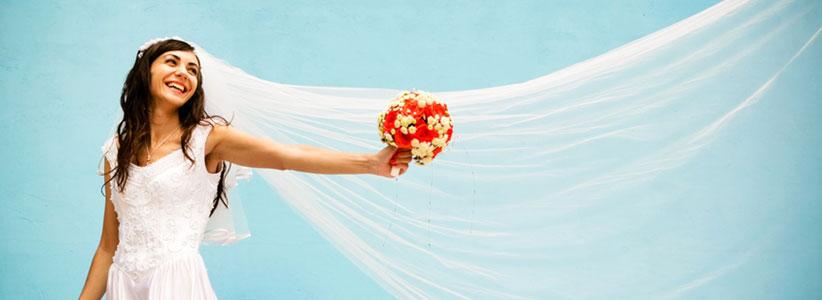 Eine Braut mit langem weißen Schleiher und Brautstrauß